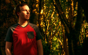 Slowtide - A Gentle Reminder - Promo Picture. Kevin Werdelmann in a forest during sunset.